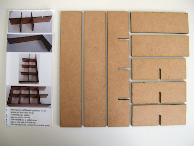 Components of a  modern dolls' house miniature laser-cut 'pidgeon' hole kit laid out on a work table.