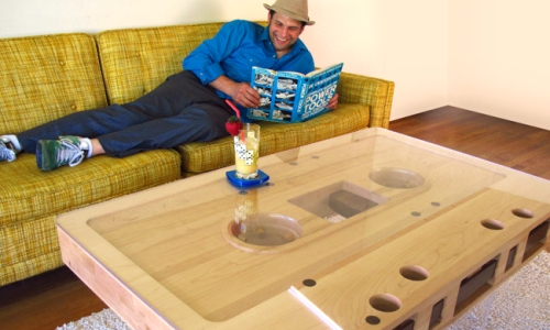 Wooden cassette tape table in living room with man on couch reading