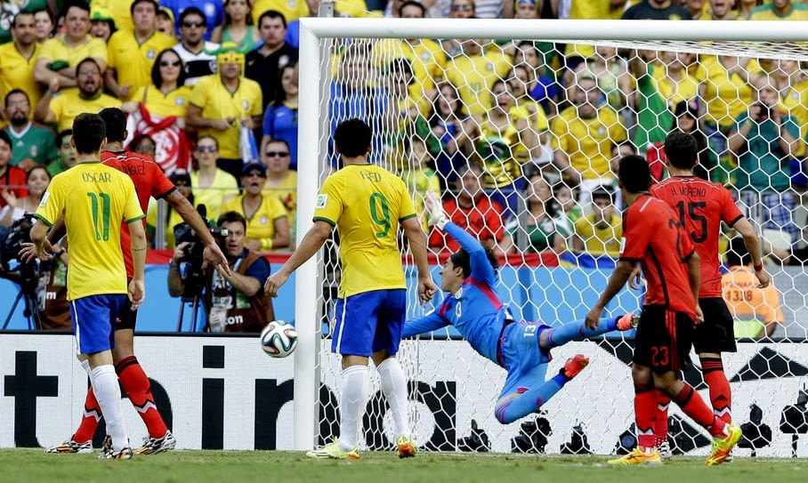 Mexico's goalkeeper Guillermo Ochoa, center, makes a save during the group A World Cup soccer match between Brazil and Mexico at the Arena Castelao in Fortaleza, Brazil, Tuesday, June 17, 2014.