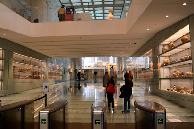 Image of the New Acropolis Museum entrance, with pottery left and right, the Archaic room ahead and the Caryatids above and a very prominent no photography sign