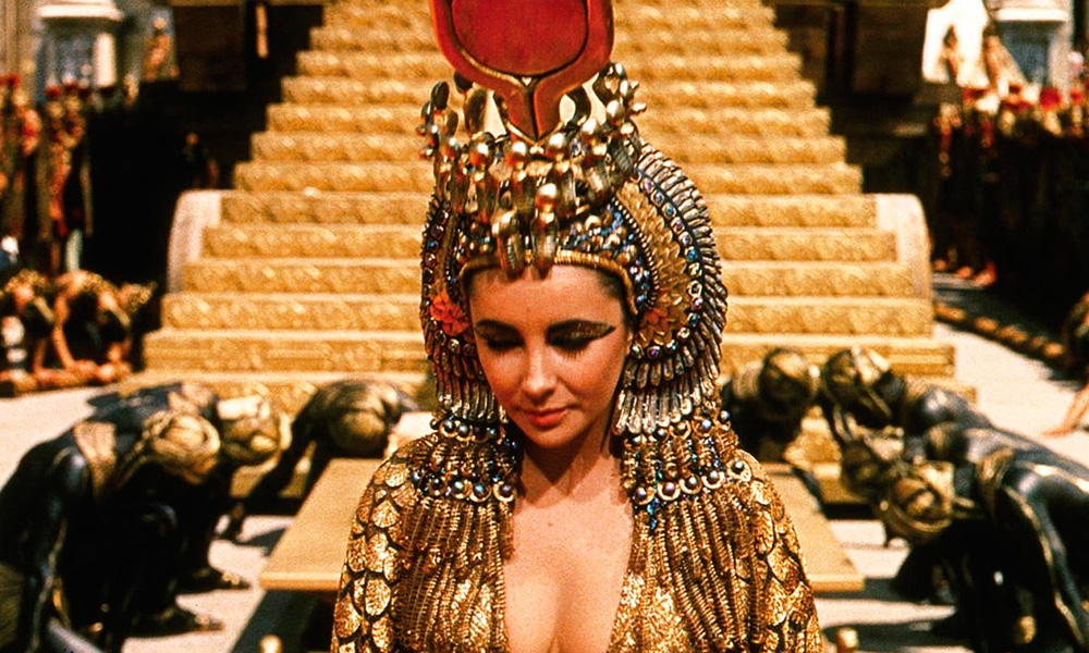 Cena do filme Cleópatra (1963) onde a rainha está em trages reais enquanto seus suditos ajoelham-se ao seu redor