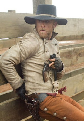 Ben Foster as Charlie Prince in 3:10 To Yuma (2007) loading his gun while hunched behind a fence.