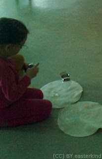 Girl struggles to keep hold of doll while opening oil jar.