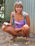Gal empties her bladder behind a garage