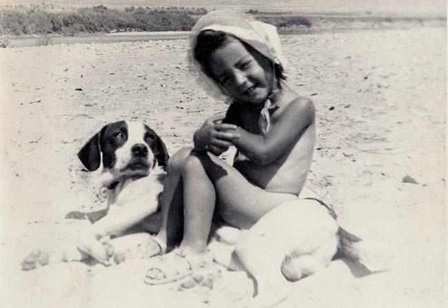 Niña en la playa con perro