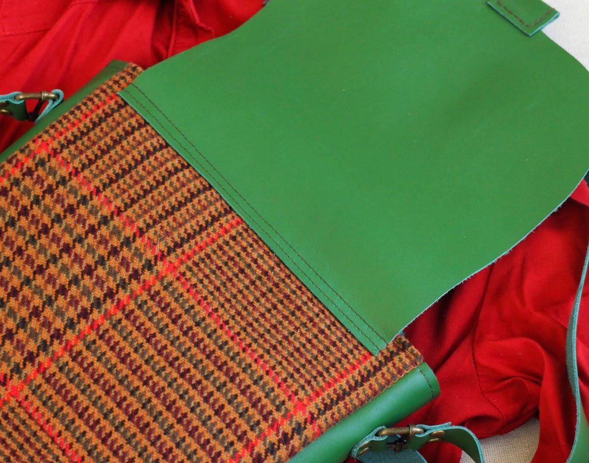 На сумке зеленый кожаный клапан, боковинки и ручка