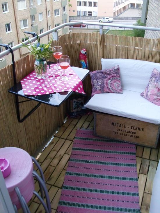 кушетка и стол на балконе вокруг цветы
