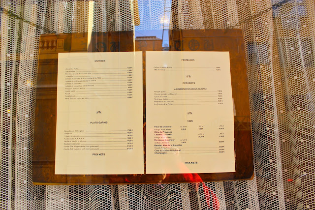 Menu chained up against a lace curtained restaurant window. A regional speciality is 'Socca', chickpea flour crepes.