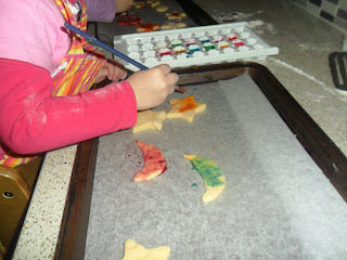 Child painting biscuit dough shapes.