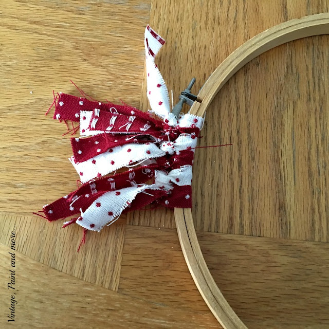 tying fabric strips onto embroidery hoop for a Valentine wreath