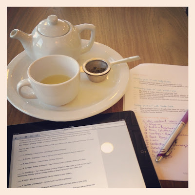 Tea on table with ipad and notes