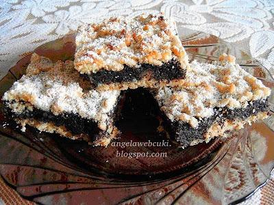 Reszelt mákos kocka sütemény, diós tésztával, citromhéjas mákos rumaromás fahéjas töltelékkel, porcukorral meghintve.