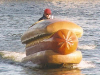A picture of a guy who looks like Phil Hellmuth riding a giant hot dog on water