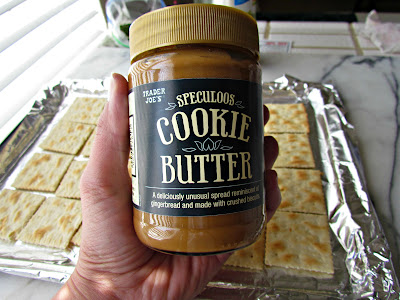 Jar of cookie butter held in a hand.