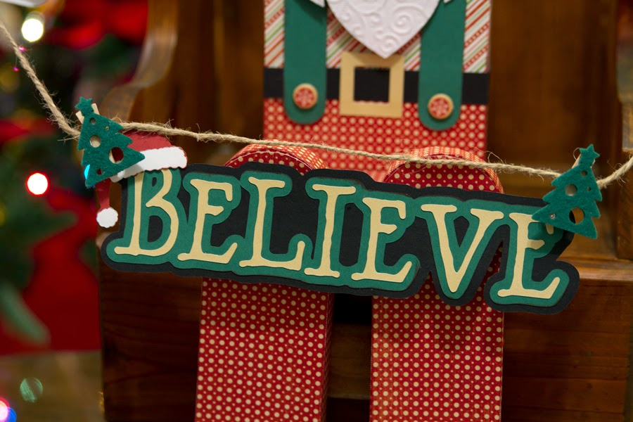 Close of sign Santa is holding that says Believe