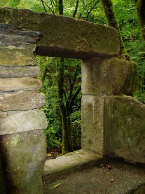 ventana de piedra en ruinas, frondoso paisaje verde detrás