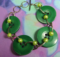 Bold button bracelet has big green buttons accented with small shiny beads linked together with silver loops