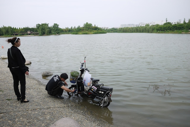 man washing motorbike while woman watches