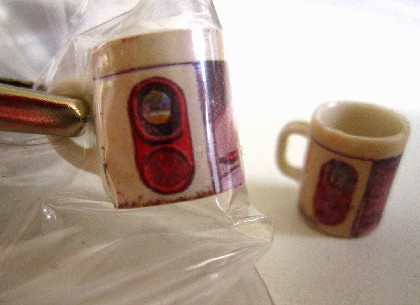 Two modern dolls' house miniature mugs with a design of a Canberra bus shelter. On the left is the (clearer) photo version, clamped to dry. On the right is the (less clear) decal version.