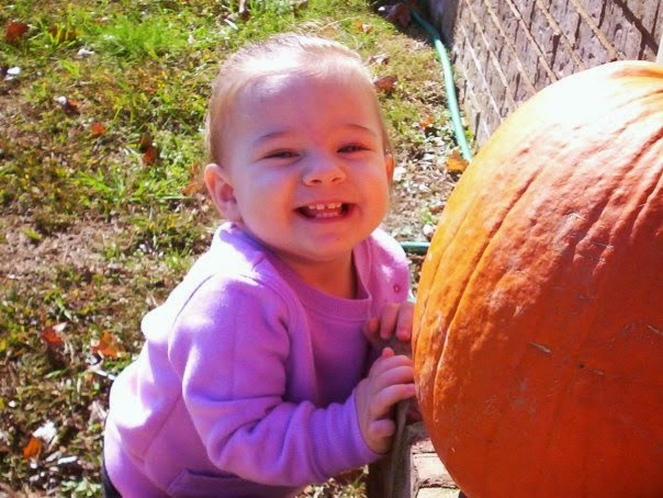 toddler girl with pumpkin