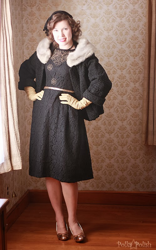 A black lace cocktail dress paired with a velvet hat, a fur coat, and sparkly gold shoes.