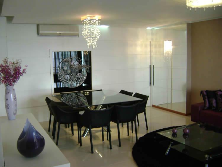 De vidro com pés de inox, cadeiras na cor preta, fica bem moderna e