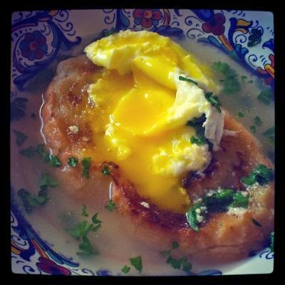 Photo of a broth-based soup surrounding a soaked piece of bread and a poached egg broken to let the yolk seep out.