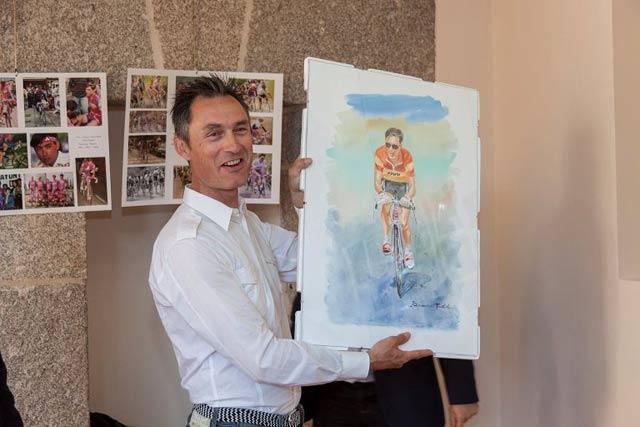 laudelino cubino sostiene un poster con un retrato suyo