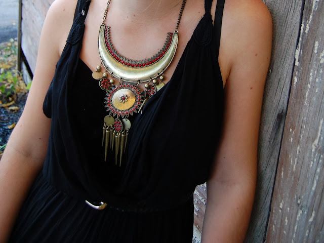 Gold statement necklace with red beads and dangling spikes and pendants worn with a black jumpsuit.