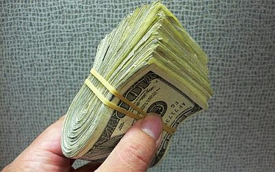 image of hand holding a wad of one hundred dollar bills