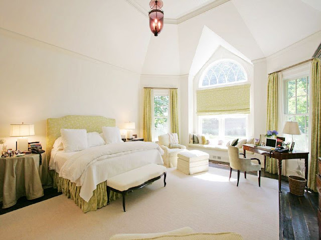 master bedroom with white walls and a high ceiling, a window seat, an green upholstered headboard with matching bed skirt, an ottoman at the foot of the bed and small home office with a rustic wood floor