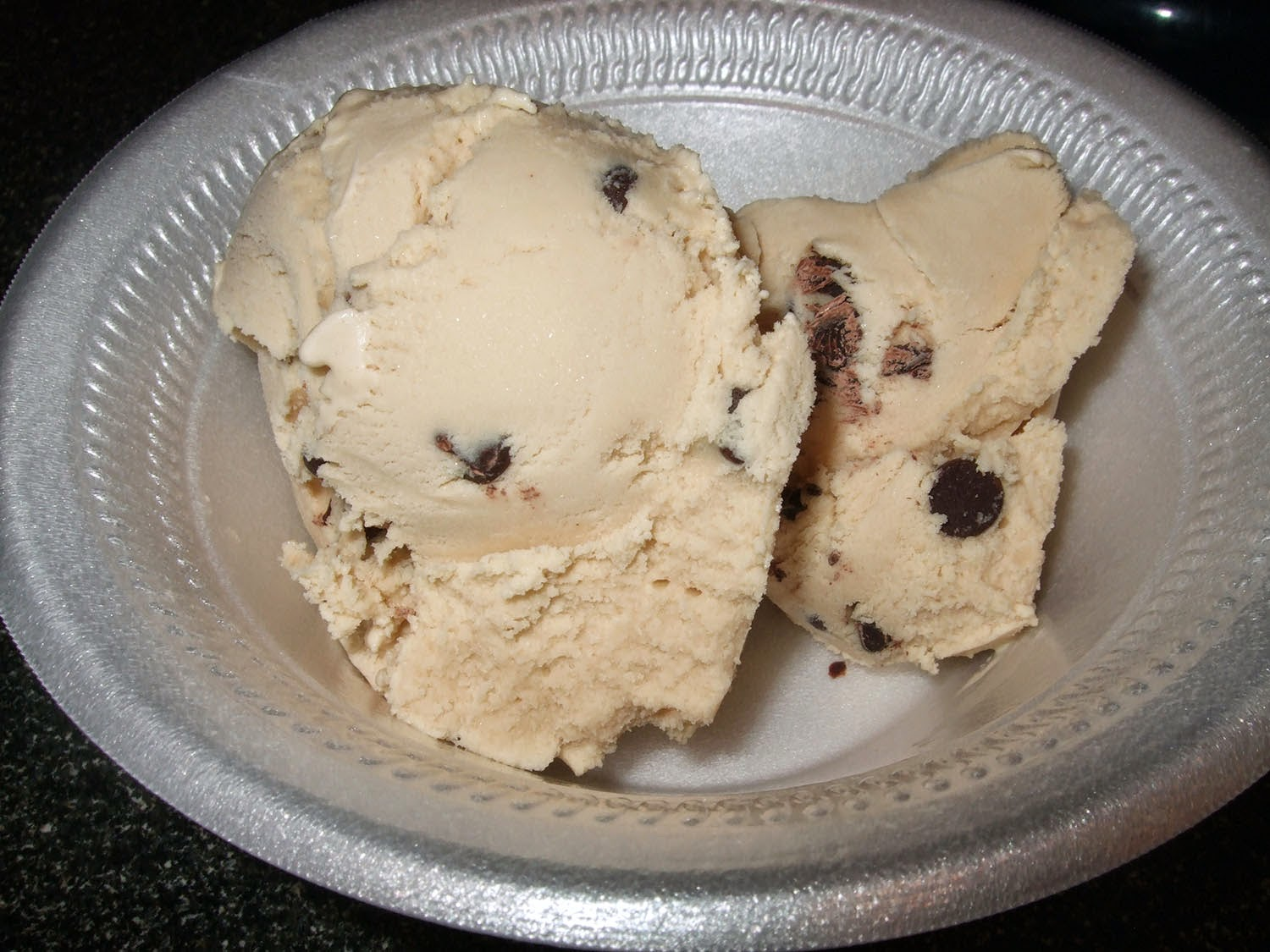 Scoop of ice cream with dark chocolate chips.
