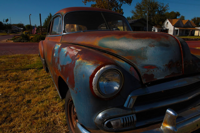 A rusted classic car parked on a lawn in Cheyenne, Wyoming.