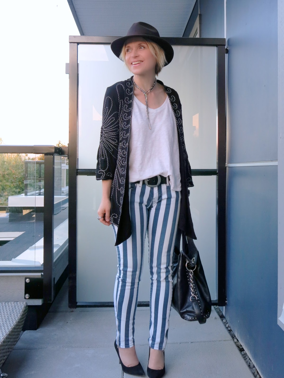 styling striped skinny jeans with an embroidered jacket, Sam Edelman pumps, and a fedora