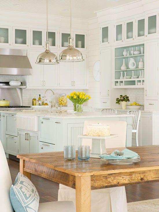 Cocina blanca con isla azul y mesa rustica