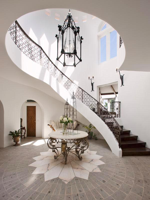 Foyer With Two Story Iron Railing Stairs A Stone Floor With A Marble