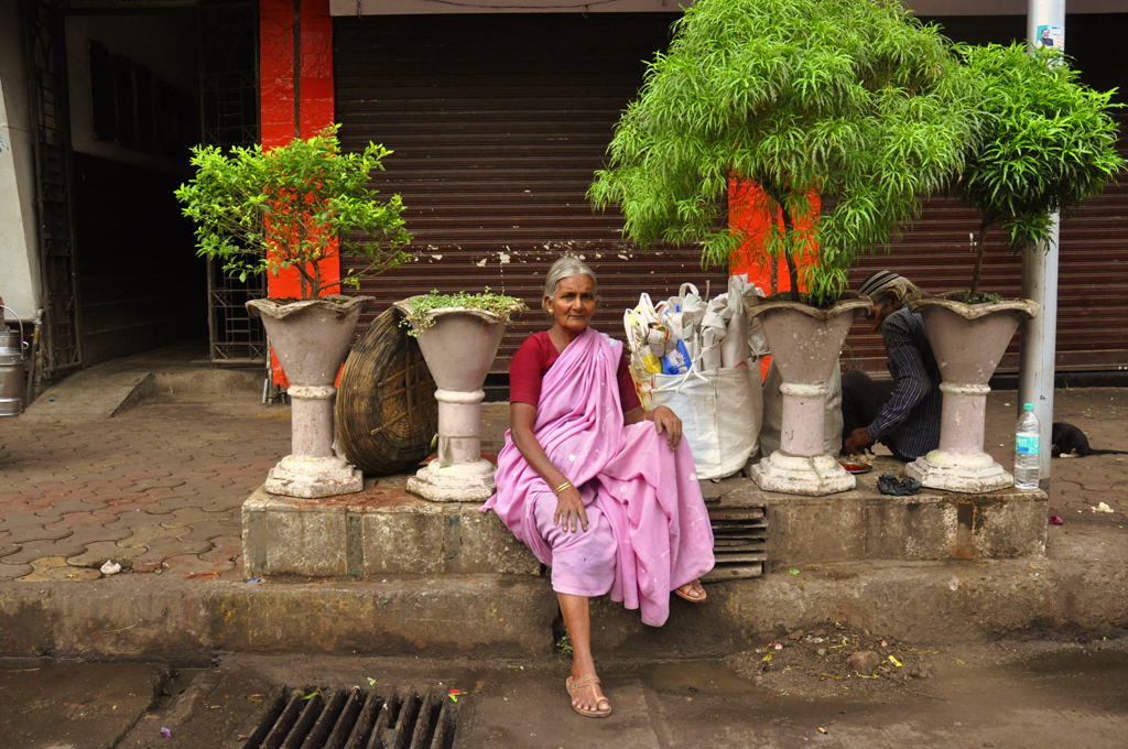 Woman waiting on the pavement in Byculla in India.