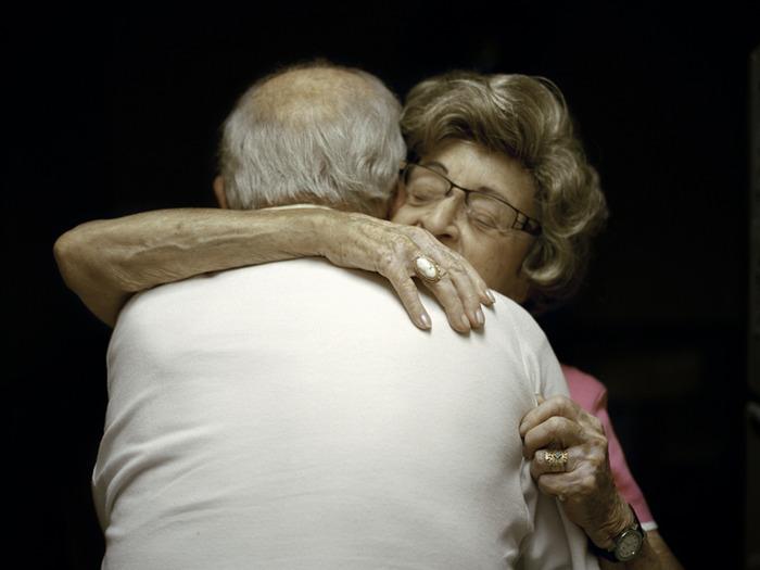 Adultos mayores en abrazo.