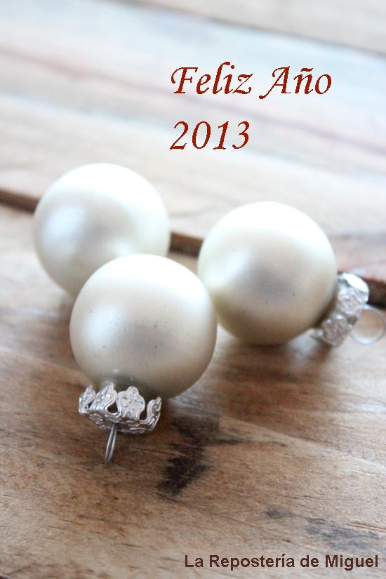 Una fotografía de tres bolas blancas de adorno navideño en un primer plano , sobre un texto de Feliz Año 2013, para desear un feliz Año nuevo.