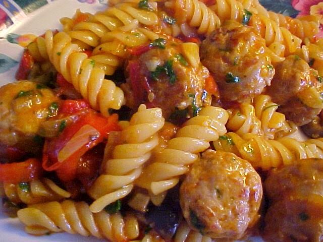 Fusilli au poivron, tomates, saucisses italiennes dans une poêle