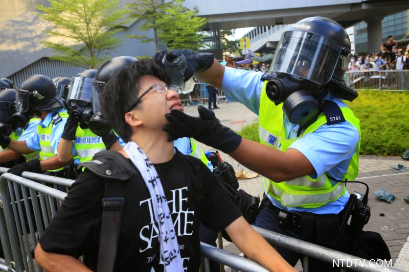 """(上图)29日下午,香港政府总部前的金钟夏悫道,这位最简单的防护装置都没有的年轻人,对向他喷射胡椒喷雾的防暴警察怒吼,""""为什么你要对我们这些手无寸铁的市民下手?""""戴上防毒面具的防暴警察、虽然看不到面孔和表情,用手轻拍愤怒的示威者,连声说""""知道,知道"""",转身拿出自己的水壶,为这位他刚刚出手伤害的市民冲洗眼睛。(余钢/大纪元)"""