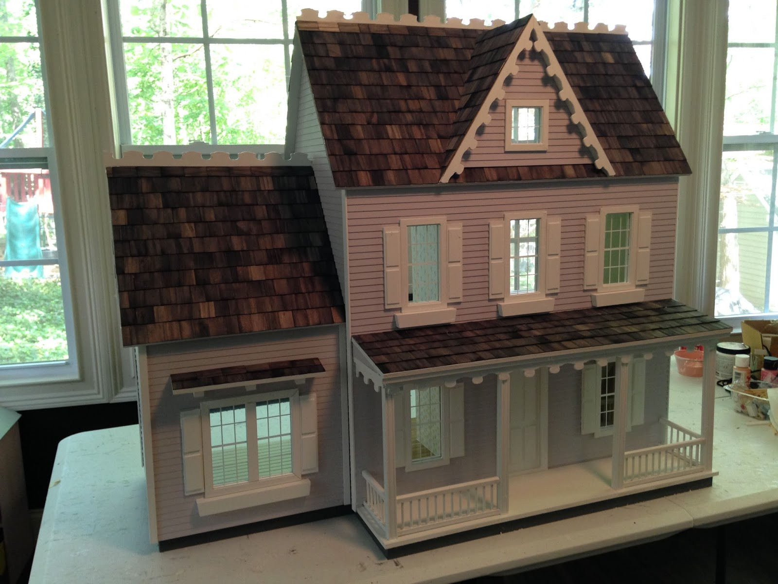 The Dollhouse Was Painted A Light Purple Color With White Trim And Gray Shingles