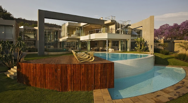 Photo of an amazing home with the pool and wooden deck as seen from the backyard