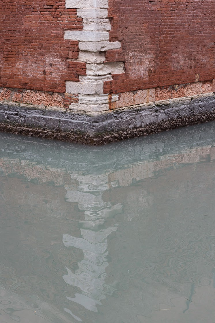 part of the Arsenale wall reflected in a Venetian canal
