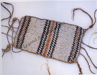 A shell disk armband (aba gwaro) from Malaita, Solomon Islands. This example of the finest shell disk jewelry from Malaita was usually worn by men at feasts and weddings. The pattern is composed of strips of disks set at alternating 45-degree angles. The beadwork demonstrates symmetry balance, and a sense of restraint, as well as workmanship of extreme precision. Strings of shell beads are found throughout the Pacific, but red, white, and black disks woven into patterns are typically Malaitan. The same weaving technique was used for bracelets, anklets, belts, and necklaces.