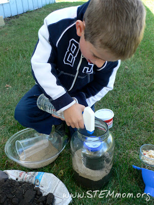 Boy spraying water in worm jar: STEMmom.org