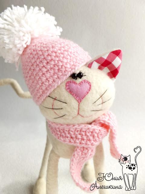 Бежевая кошка длинноножка - в розовой шапке. Портрет