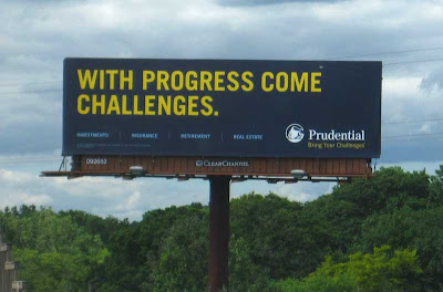 Dark blue billboard with yellow letters reading WITH PROGRESS COME CHALLENGES