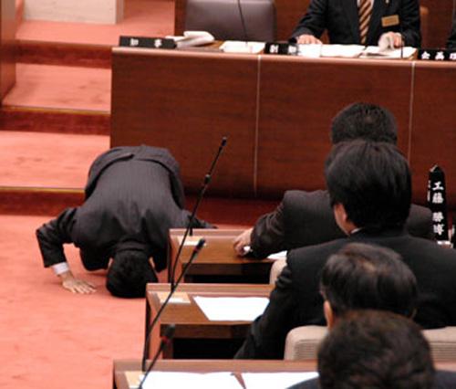 Seorang anggota parlemen Jepang yang sedang berlutut didepan rekan-rekannya