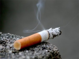 a cigarette slowly smokes and burns as it dangles off of stone